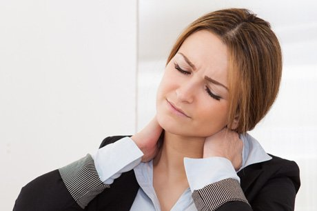 Woman holding neck, pain shown on her face